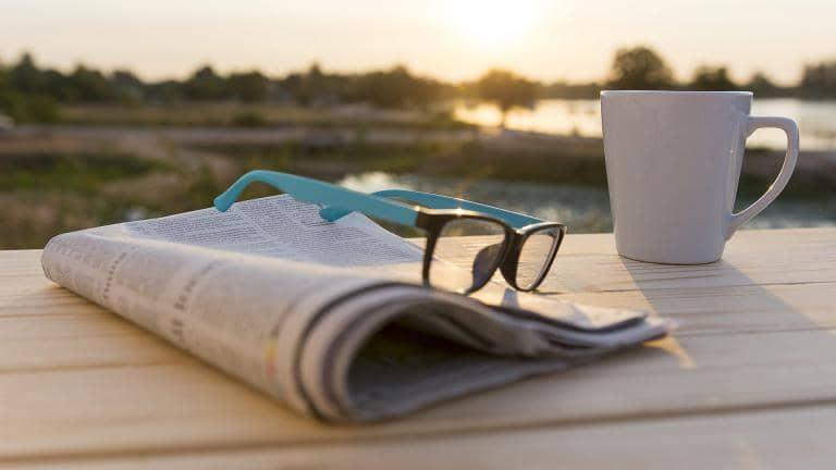 Image of a newspaper, pair of glasses and a mug
